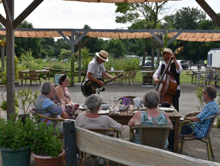Gasten van De Maretak eten, drinken en genieten van muziek